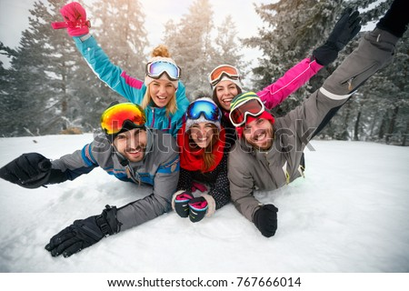 Happy skiers lying on snow and having fun