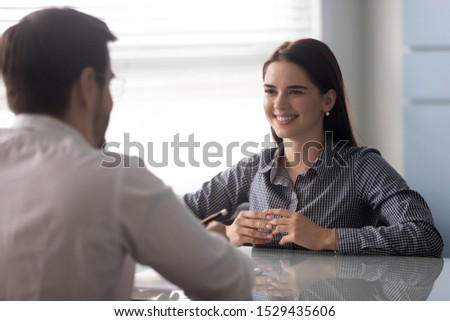 Happy skilled young female job candidate performing herself on interview with company hr manager at office. Smiling woman listening to questions of employer, making good first impression at meeting.