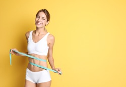 Happy slim woman in underwear with measuring tape on color background. Positive weight loss diet results