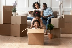 Happy small african American kids play riding in cardboard boxes feel excited to move in new house, playful overjoyed black brother and sister have fun, young parents relax on couch on relocation day