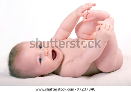 happy small baby isolated on white, playing with own legs