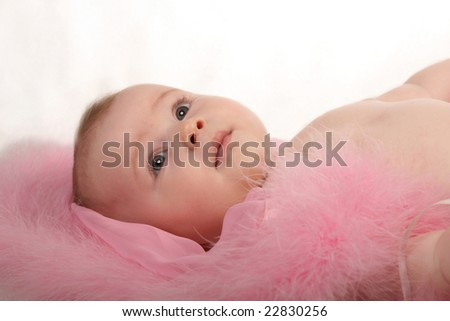 happy small baby lying on pink silk blanket