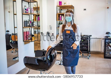 Happy small business owner at a hairdressing studio during COVID-19. Portrait of elegant hair salon employee in apron with medical mask, gloves, hair comb and scissors.