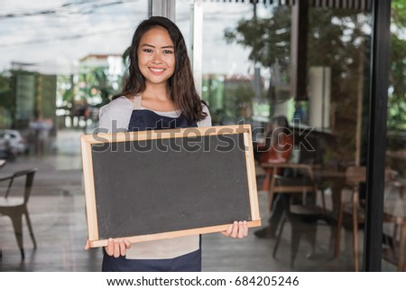 happy small business owner ready to open her cafe for the first time. holding chalk board