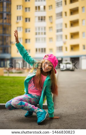 Happy small child jumping active for pleasure. Active and energetic girl having fun in summer. The concept of sports, dance, hip hop.