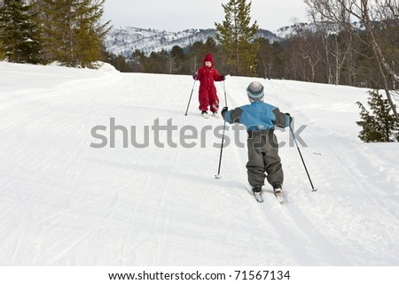 Happy small children meeting in the ski tracks