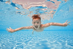 Happy small cute boy swim and dive underwater, kid breast stroke with fun in pool. Active healthy lifestyle, water sport activity and lessons with parents on summer family vacation with child.