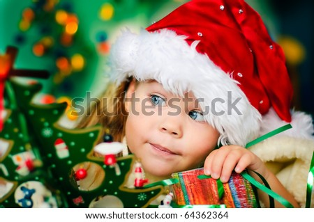 Happy small girl in santa hat with present have a christmas