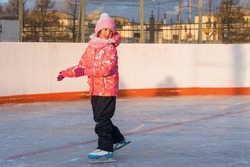 Happy  small girl is skating on the court on a winter evening in the rays of the setting sun