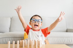 Happy smart and nerd toddler asian boy raised hand when he win play wooden toy block at home.Boy child kid wearing glasses.myopia or Short sighted.Positive human emotion, Attitude and self esteem.