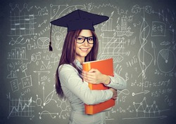 Happy smart girl student with graduation cap and folder over high school math and science formulas on blackboard