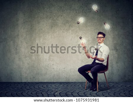 Happy smart man sitting on chair against gray concrete wall and juggling with light bulbs having many brilliant ideas. #1075931981