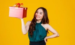 Happy smile face cute Asian girl with dark hair holding gift box with delightful and excited, studio shot on yellow background. Celebrate and festival concept