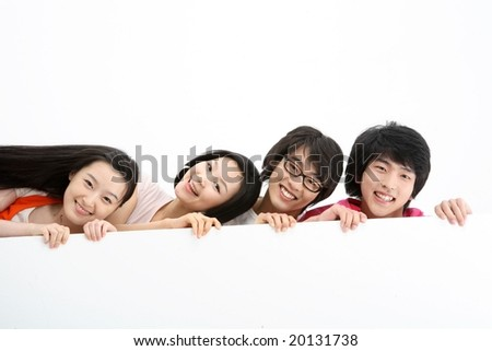 Happy smile group of joyful four young people holding and showing a blank, empty card board with modern life style isolated on white background