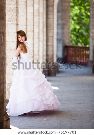 Happy smile of the young fair-haired girl in a pink wedding dress.  Summer garden, avenue with columns.