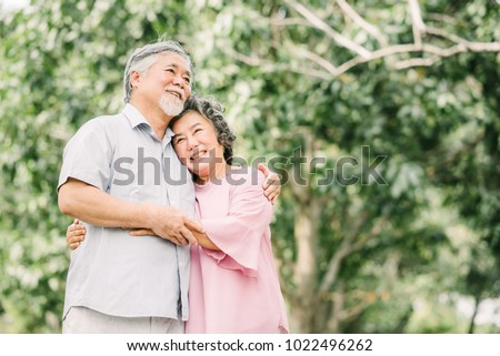 Happy smile senior Asian couple enjoying quality time together and holding each other in the park.