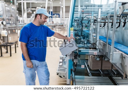 Happy smiled worker doing his job on Robotic factory line for processing and quality control in water factory.
