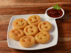 Happy Smiley French Fries with tomato ketchup served in a plate over a rustic wooden background, selective focus