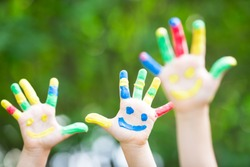 Happy smiley hands against green spring background