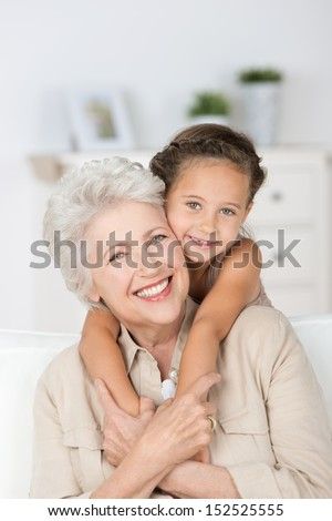 Happy smiling affectionate grandmother and her cute little granddaughter giving each other a loving hug as they smile at the camera