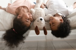 Happy smiling african american children boy and girl with soft toy laying upside down on bed, joking, having fun, looking at each other, fooling at home, enjoying free playtime together.