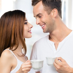 Happy smiling amazed couple with cups of coffee or some drinks at home. Portrait of standing close and looking at each other models in love family concept. Man and woman posing together. Square photo.