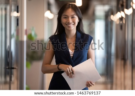 Happy smiling asian businesswoman looking at camera holding papers stand in office hallway, happy confident chinese professional executive satisfied with good career posing in modern office, portrait