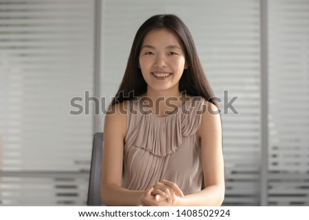 Happy smiling asian businesswoman looking at camera sit at office desk, korean professional teacher trainer coach webinar speaker recording vlog communicating via conference video call with client