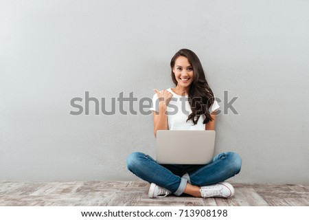 Happy smiling asian woman working on laptop computer while sitting on the floor with legs crossed and pointing finger away isolated over gray background