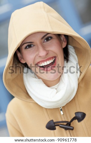 Happy smiling attractive woman with hood in winter