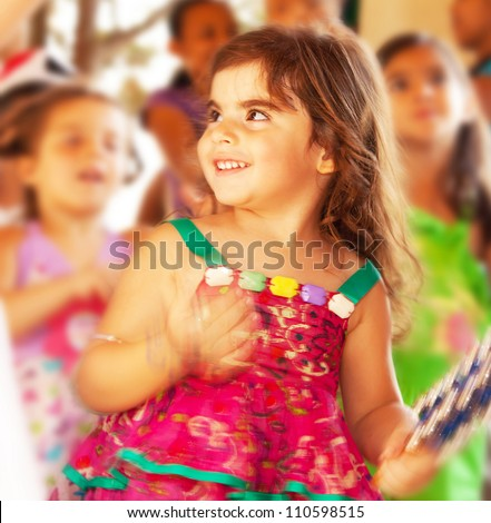 Happy smiling baby girl, adorable cheerful female child enjoying dance on carnival festival, sweet kid having fun on birthday party outdoor, pretty little girl portrait, happiness concept
