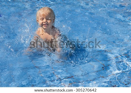 Happy smiling baby has fun jumping with splashes in blue water in pool before swimming lessons. Healthy lifestyle, active parents, and people water sports activity on summer family vacation with baby.