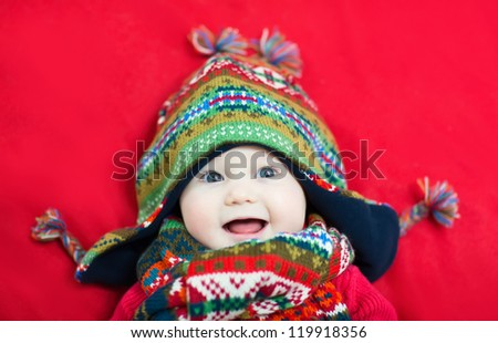 Happy smiling baby in a funny colorful hat and scarf