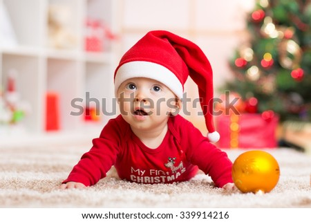 Happy Smiling baby lying against domestic festive backdrop with Christmas tree. Cute kid wearing Christmas Santa hat and suit