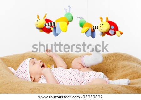 Happy smiling Baby lying on blanket and Playing with toys