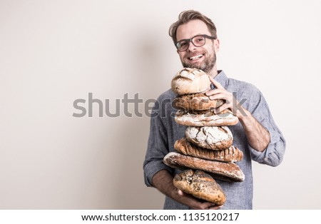 Happy smiling baker man holding pile of rustic crusty loaves of bread. Small business and slow food concept. White background with free (copy) text space.