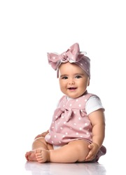 Happy smiling barefooted Infant baby toddler in polka-dot dress and headband with bow sits on the floor holding hand at her leg touching. Happy infancy and babyhood concept