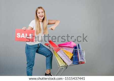 happy smiling beautiful blonde girl with sale sign and pushcart full of colorful shopping bags isolated over grey