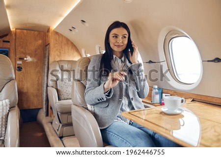Happy smiling beautiful business woman in private jet Foto stock ©
