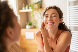 Happy smiling beautiful girl cleaning skin face with cotton pad. Beauty natural woman looking in mirror while cleansing skin face and using cosmetic products for properly deep clean.