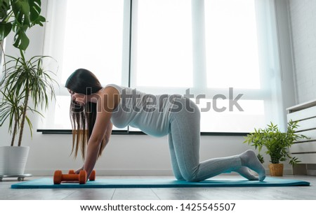 Happy smiling beautiful pregnant woman exercising at home