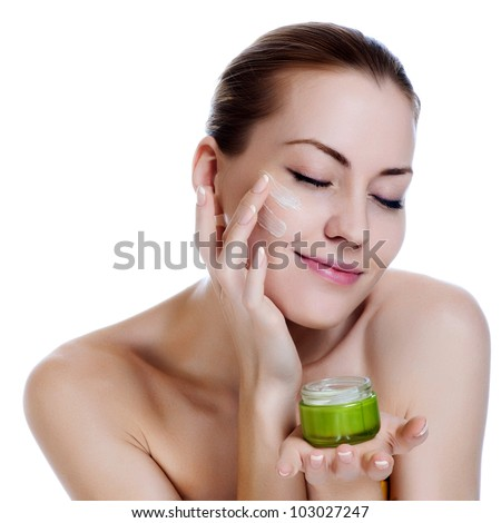Happy smiling beautiful woman applying moisturizer cream on the face