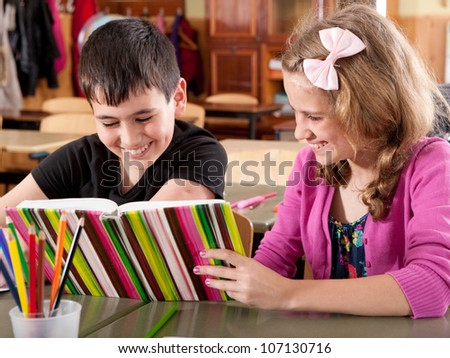 Happy smiling boy and girl reading book at school during a lesson