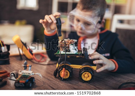 Happy smiling boy constructs technical toy. Technical toy on table full of details #1519702868