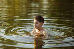 Happy smiling boy having fun swimming in the water