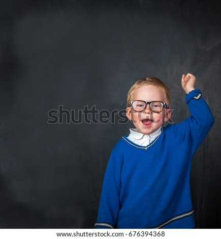 Happy smiling boy in glasses with hand up. Happy exited boy having fun in class room with blackboard ona background. Back to school. #676394368