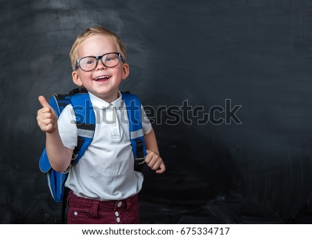 Happy smiling boy in glasses with thumb up is going to school for the first time. Child with school bag and book. Kid indoors of the class room with blackboard on a background. Back to school. #675334717