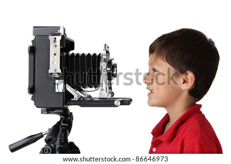 Happy smiling boy in red shirt looking into old press camera on white background