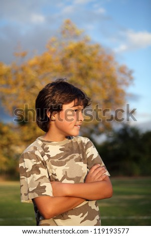 Happy smiling boy in the park near to sunset with shallow depth of field and copy space at top