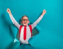 Happy smiling boy in uniform breaking through yellow paper wall. Happy smiling kid go back to school, kindergarten. Success, motivation, winner, genius concept. Little kid dreaming to be superhero.